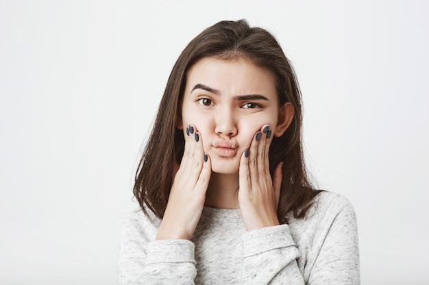Jeune modèle féminin européen attrayant serrant ses joues avec une expression perplexe et douteuse