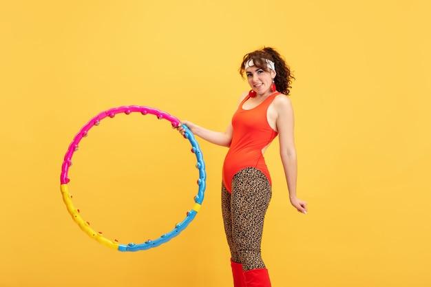 Jeune modèle féminin de taille plus caucasienne s'entraînant sur jaune