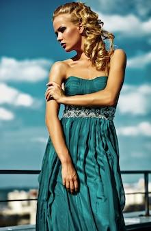 Jeune modèle femme blonde sexy en robe de soirée posant sur ciel bleu