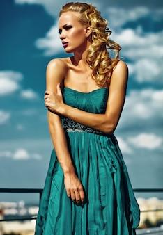 Jeune modèle femme blonde sexy en robe de soirée posant sur le mur de ciel bleu