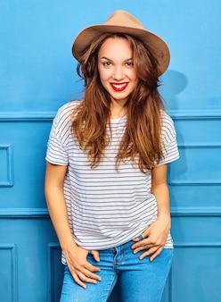 Jeune modèle femme élégante dans des vêtements d'été décontractés et un chapeau brun avec des lèvres rouges, posant près du mur bleu