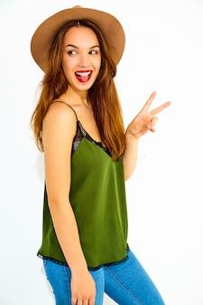 Jeune modèle femme élégante dans des vêtements d'été vert décontracté et un chapeau brun avec des lèvres rouges, montrant le signe de la paix et sa langue