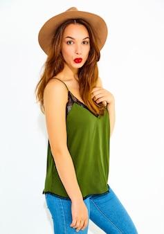 Jeune modèle femme élégante en vêtements d'été vert décontracté et chapeau brun avec des lèvres rouges, posant près du mur blanc