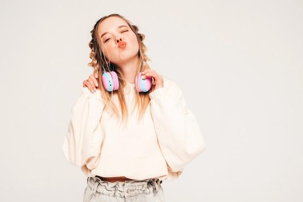 Jeune modèle insouciant écoutant de la musique dans des écouteurs sans fil