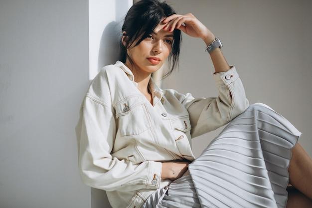 Jeune modèle de jolie femme assise près du mur
