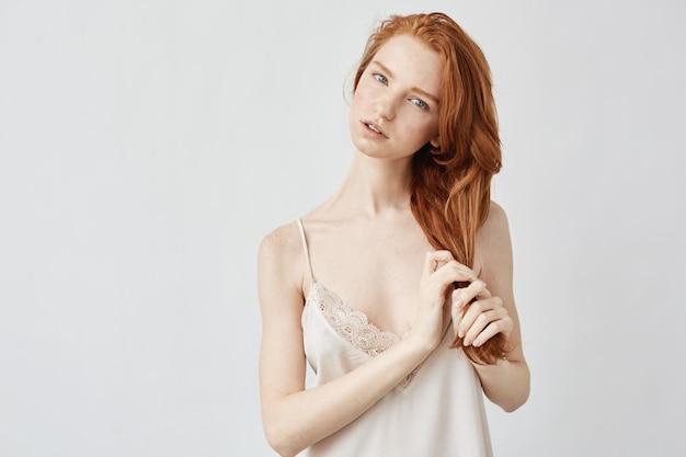 Jeune modèle rousse tendre touchant les cheveux.
