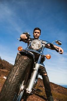 Jeune motard assis sur sa moto en regardant la caméra