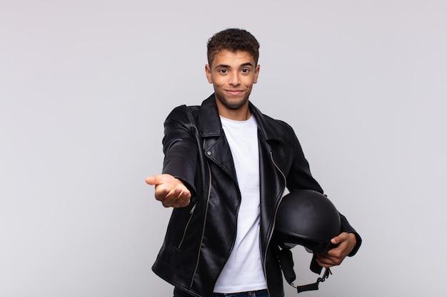 Jeune motard souriant joyeusement avec un regard amical, confiant et positif, offrant et montrant un objet ou un concept