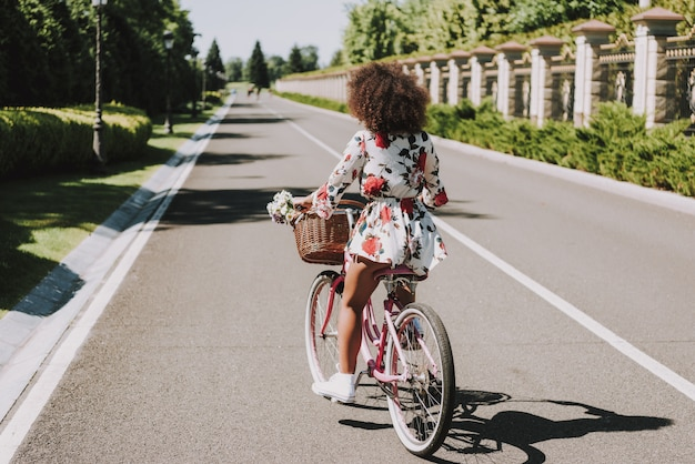 Jeune mulatta en robe à fleurs fait du vélo dehors.