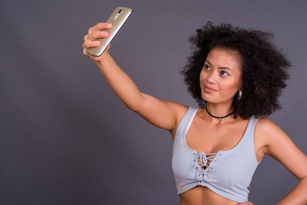 Jeune, multi ethnique, femme américaine africaine, à, cheveux afro, contre, mur gris