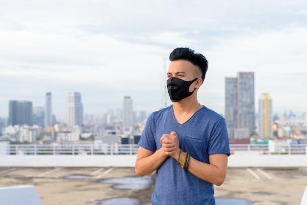 Jeune, multi, ethnique, homme, porter, masque, mains jointes, contre, vue, ville