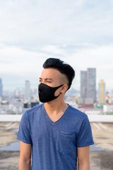 Jeune, multi, ethnique, homme, porter, masque, pensée, contre, vue, ville