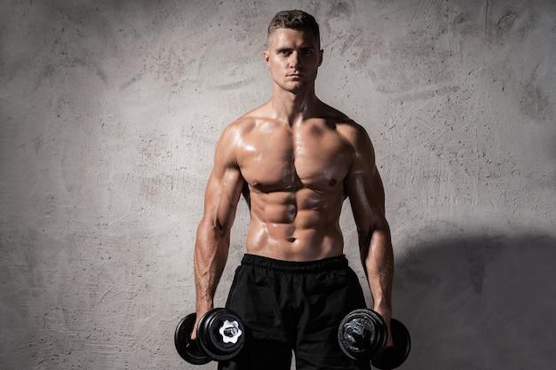 Jeune et musclé bodybuilder travaillant avec des haltères