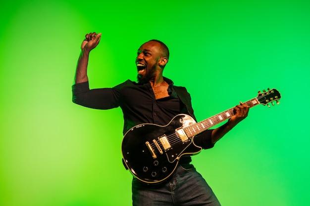 Jeune musicien afro-américain jouant de la guitare comme une rockstar sur fond dégradé vert-jaune. concept de musique, passe-temps, festival, plein air. un gars joyeux improvise, chante une chanson.