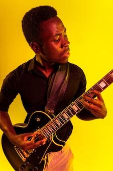 Jeune musicien afro-américain jouant de la guitare comme une rockstar sur un mur jaune à la lumière du néon.