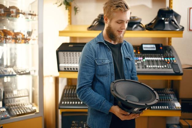 Jeune musicien barbu achetant un haut-parleur de subwoofer dans un magasin de musique. assortiment dans le magasin d'instruments de musique, musicien masculin choisissant le clavier