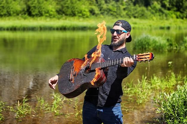 Un jeune musicien barbu à lunettes de soleil veut jouer d'une guitare brûlante, mais a peur de se brûler. le guitariste essaie de jouer de la guitare en proie aux flammes, mais la flamme est trop chaude.