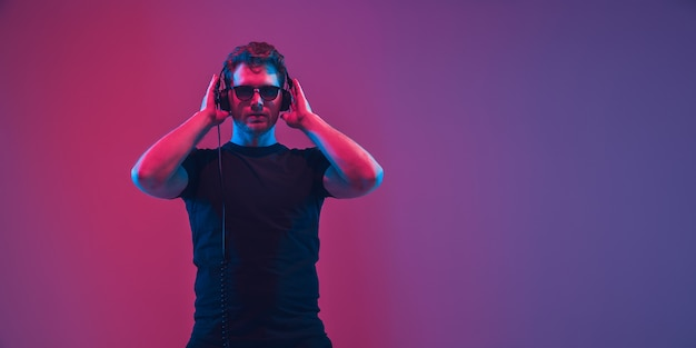 Jeune musicien caucasien au casque chantant sur un mur dégradé rose-violet à la lumière du néon. concept de musique, passe-temps, festival. hôte de fête joyeux, dj, debout. portrait coloré de l'artiste.