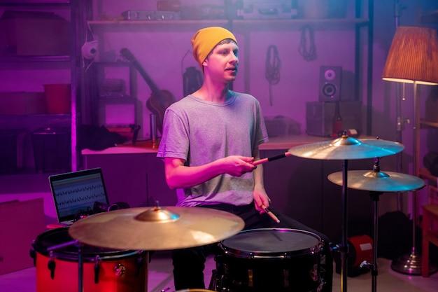 Jeune musicien contemporain en tenue décontractée battant des cymbales et des tambours avec des baguettes