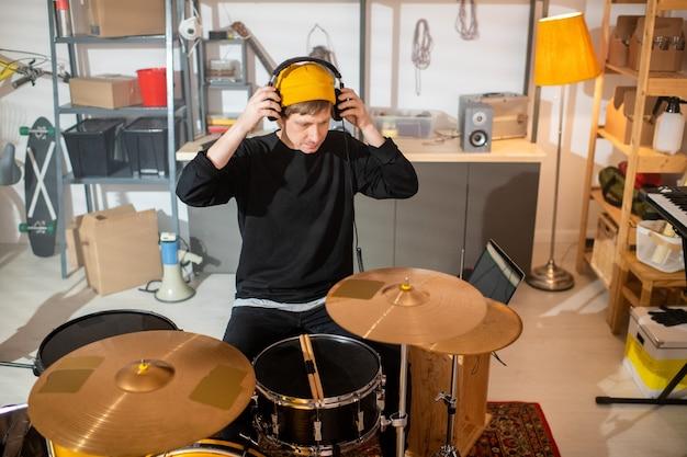 Jeune musicien contemporain en tenue décontractée mettant des écouteurs assis par kit de batterie et va avoir une répétition individuelle dans le garage