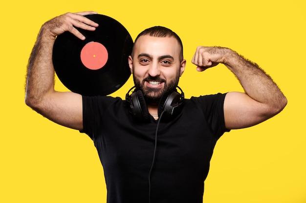 Jeune musicien dj arabe souriant tenant un disque vinyle dans les mains et montrant les muscles jaune