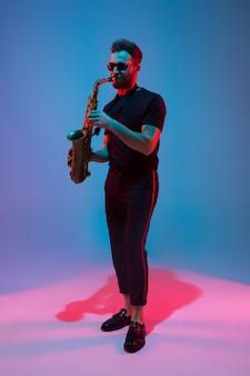 Jeune musicien de jazz caucasien jouant du saxophone sur fond de studio bleu-violet dégradé à la lumière du néon. concept de musique, passe-temps, festival. mec attrayant joyeux. portrait coloré de l'artiste.