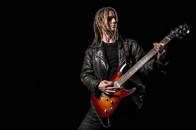 Jeune musicien masculin avec des dreadlocks jouant de la guitare électrique sur fond noir