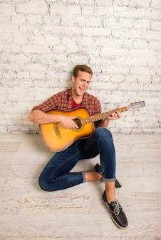 Jeune musicien sur le sol avec guitare et chant