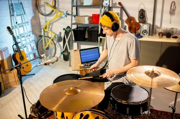 Jeune musicien en t-shirt et bonnet frappant des tambours et des cymbales avec des baguettes