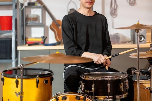 Jeune musicien en tenue décontractée battant l'un des tambours avec des baguettes en bois alors qu'il était assis par kit de batterie pendant les répétitions dans le garage