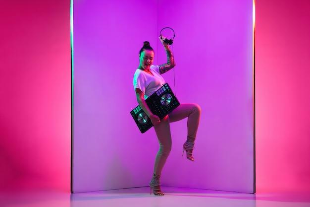 Jeune musicienne au casque sur fond violet à la lumière du néon. concept de musique, passe-temps, festival, divertissement, émotions. hôte joyeux, dj, portrait d'artiste.