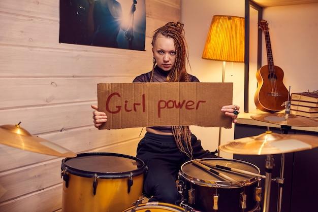 Jeune musicienne de rock tenant une affiche en carton sur le pouvoir des filles