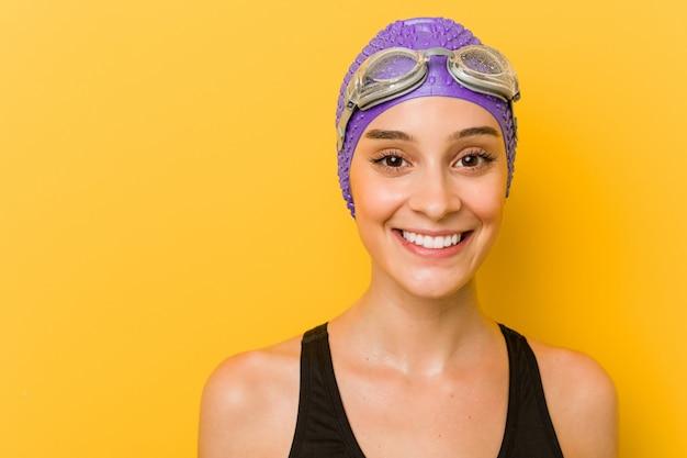Jeune nageur caucasien femme contre jaune
