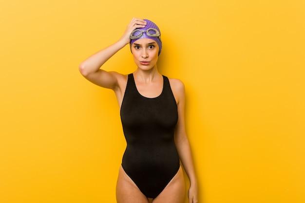Jeune nageur caucasienne femme fatiguée et très fatiguée, gardant la main sur la tête.