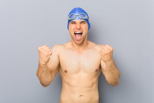 Jeune nageur professionnel acclamant sans soucis et excité. concept de victoire.