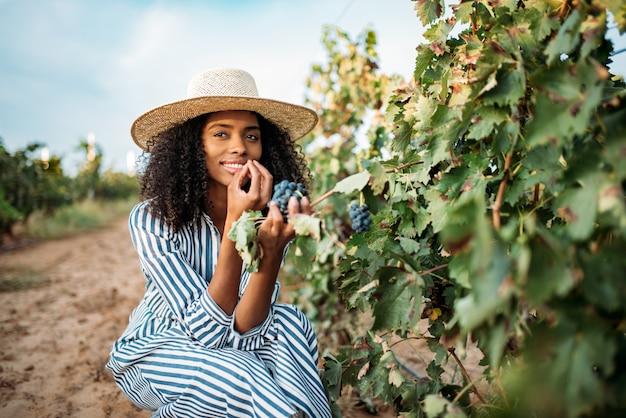 Jeune, noir, femme, manger, raisin, vignoble