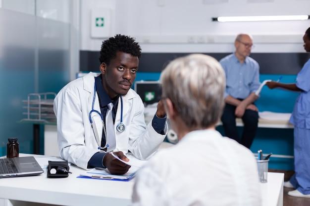 Jeune noir avec profession médicale consultant une vieille femme