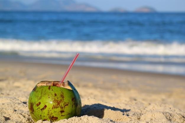 Jeune noix de coco fraîche avec une paille sur la plage de sable, avec un océan flou en arrière-plan