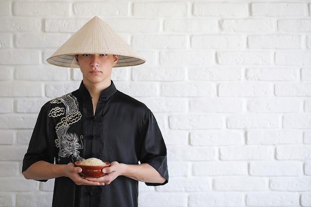 Jeune novice asiatique sur un fond de mur de briques blanches