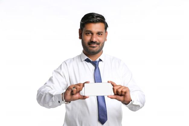 Jeune officier indien montrant l'écran du smartphone sur fond blanc.