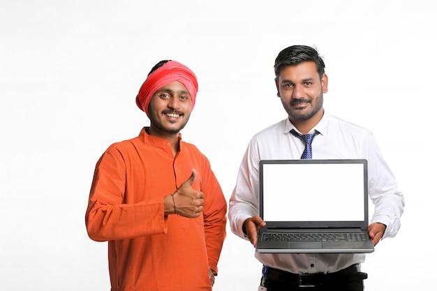 Jeune officier indien montrant un écran d'ordinateur portable avec un agriculteur sur fond blanc.
