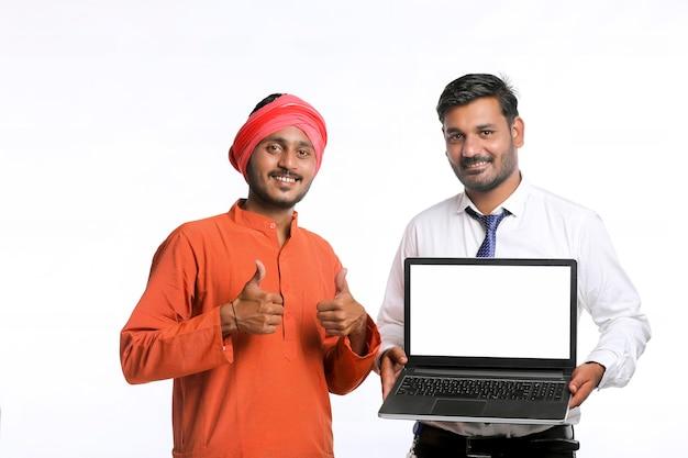 Jeune Officier Indien Montrant Un écran D'ordinateur Portable Avec Un Agriculteur Sur Fond Blanc. Photo Premium
