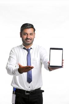 Jeune officier indien montrant l'écran de la tablette sur fond blanc.