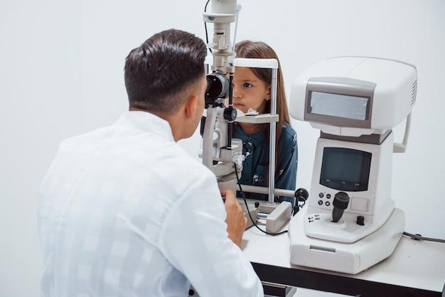 Le jeune ophtalmologiste est avec une petite visiteuse à la clinique.