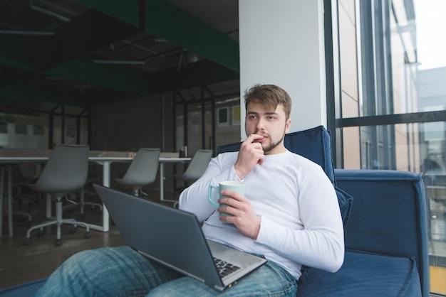 Jeune avec un ordinateur portable et une tasse de boisson chaude assis sur le canapé et pensant.