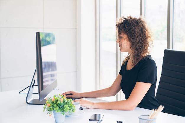 Jeune ouvrier créatif caucasien travaillant sur ordinateur de bureau à la maison