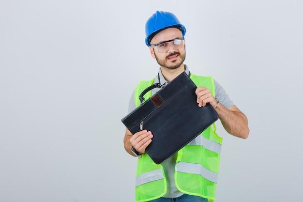 Jeune ouvrier du bâtiment dans un casque de sécurité et des lunettes