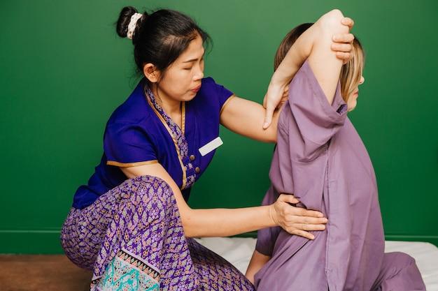 Jeune ouvrier masseur thaïlandais fille en costume exotique asiatique ethnique fait et démontre différentes procédures de spa traditionnel dans la salle de yoga de relaxation verte