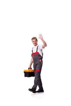 Jeune ouvrier portant des combinaisons isolées sur blanc