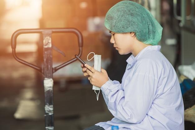 Une jeune ouvrière birmane asiatique s'assoit et se détend, joue au téléphone portable, attend des quarts de travail dans une usine d'hygiène alimentaire.